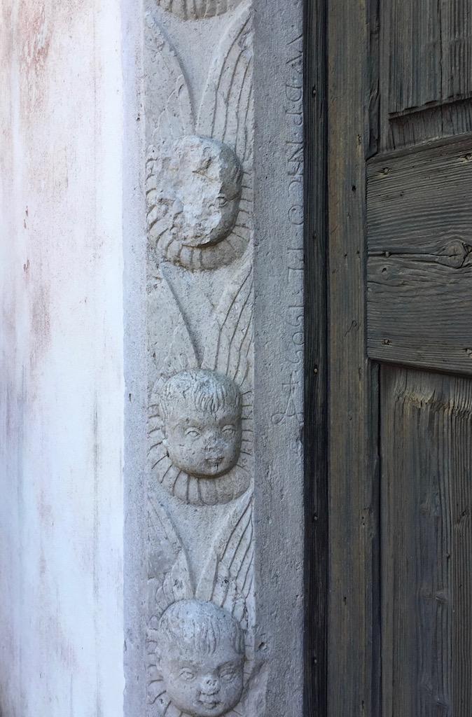 Il portale è contornato da 18 teste di angeli privi di corpo, che portano le loro ali avvolte intorno al collo come gorgere